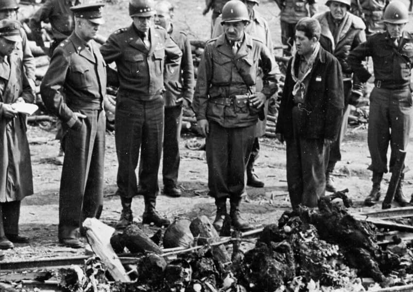 General Dwight Eisenhower and a party of high ranking U.S. Army officers, including Generals Bradley, Patton, and Eddy, view the charred remains of prisoners that were burned upon a section of railroad track during the evacuation of the camp. April 12, 1945.