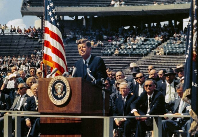 President John F. Kennedy giving a speech about space exploration with Vice President Lyndon B Johnson and others looking on.