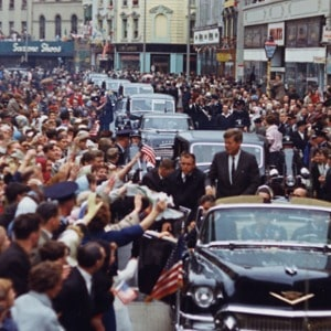 President John F. Kennedy greets spectators as he travels in his motorcade in Patrick Street, Cork, Ireland. 28 June 1963.  Robert Knudsen.